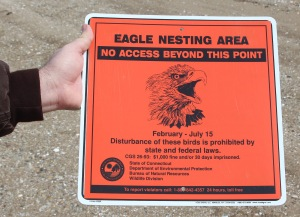Hour photo/Chris Bosak Rick Potvin, manager of the Stewart B. McKinney NWR, holds a sign before it was posted on Chimon Island on Wednesday. The U.S. Fish & Wildlife officials were on the island to mark off areas to protect a bald eagle nest.